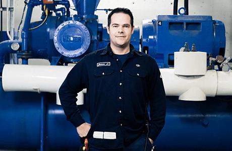 F. Ménard | Électromécanicien en habit de travail posant devant de la machinerie