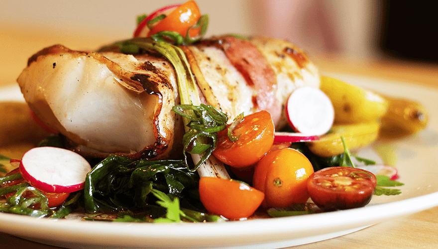 F. Ménard | Filet de poisson enrobé de bacon servi avec légumes en accompagnement