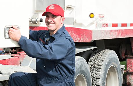 F. Ménard | Transporteur F. Ménard en chienne de travail bleue posant devant un camion