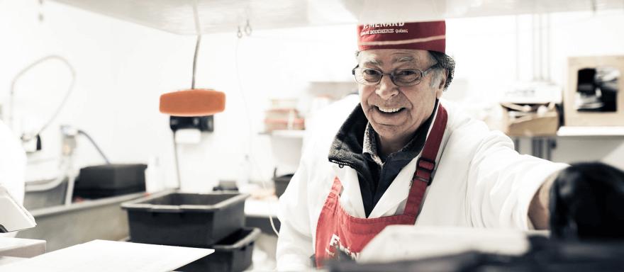 F. Ménard | Homme souriant en sarrau blanc et tablier rouge dans une boucherie blanche